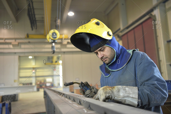 Welder checking metal surface in factory