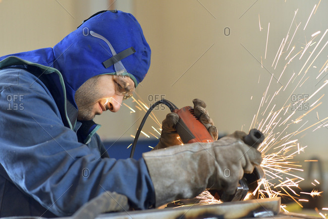 Worker using angle grinder in factory