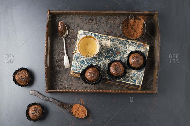 Small cupcakes with chocolate cream and cocoa powder