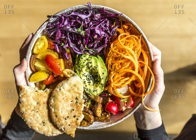 Girl holding veggie bowl with tomato- tofu- red cabbage- avocado- carrot- red redish- cress- black sesame and pita bread