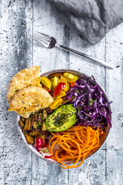 Veggie bowl with tomato- tofu- red cabbage- avocado- carrot- red redish- cress- black sesame and pita bread