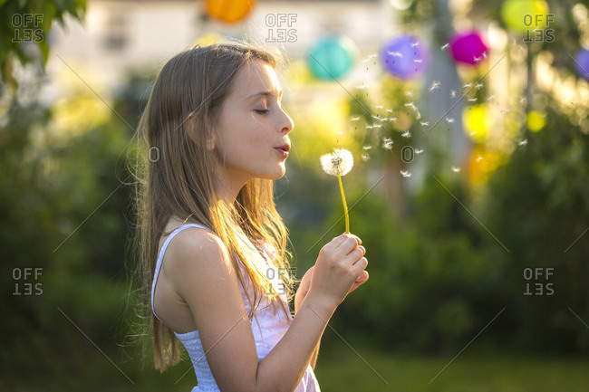 Girl blowing blowball in the garden