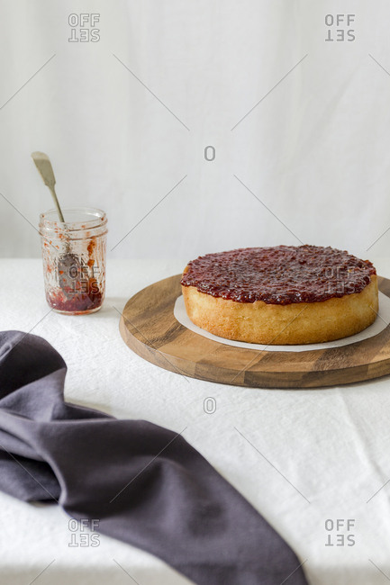 Jam on sponge cake with a jam jar on the side