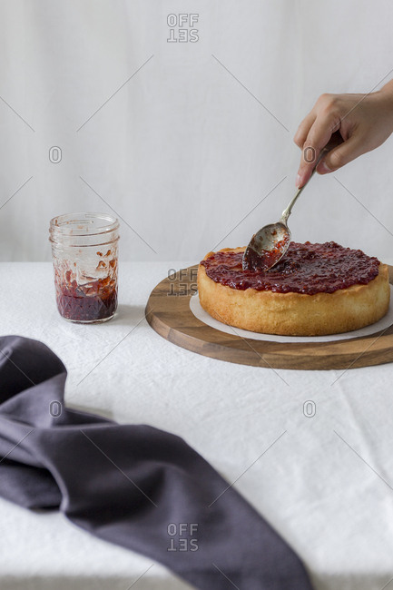 Person spreading jam on sponge cake