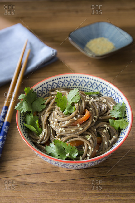 Bowl of soba noodles with sesame seeds and chopsticks