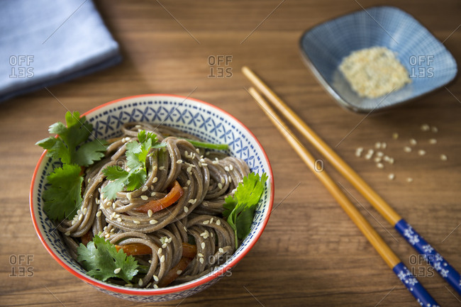Bowl of soba noodles with sesame seeds and chopstick
