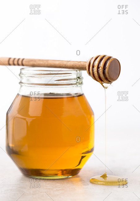 Jar of honey with dipper dripping