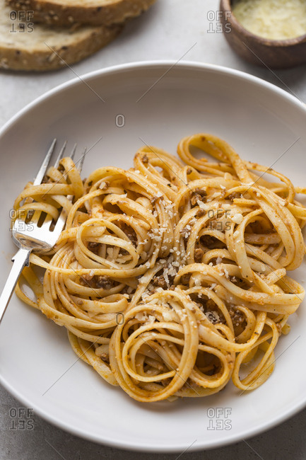Bowl of spaghetti with pasta twirl on fork, bread and cheese on the side