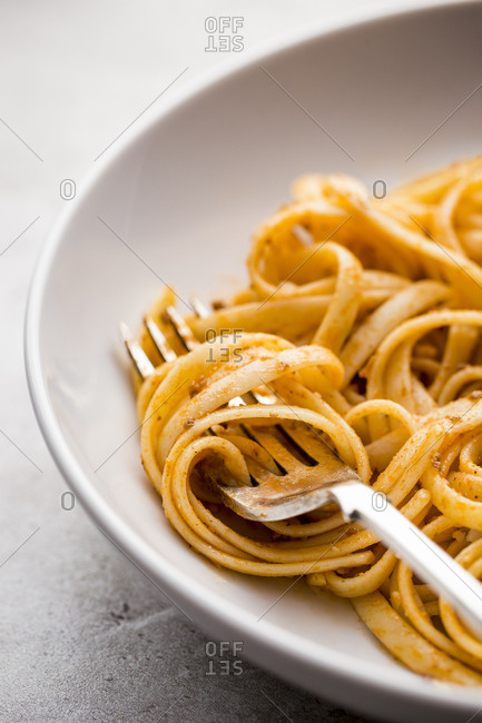 Pasta twirl on fork with a bowl of pasta