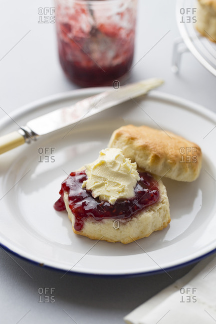 Baked scones with jam and clotted cream, jam jar