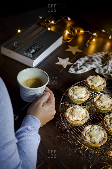 Person enjoying Christmas hygge with mince pies and coffee