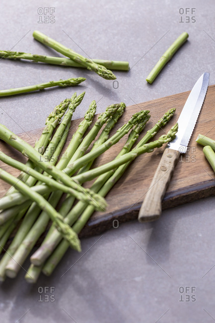 Asparagus being cut on wooden board with a knife