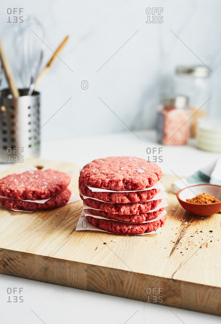 Stack of raw meat patties with seasoning