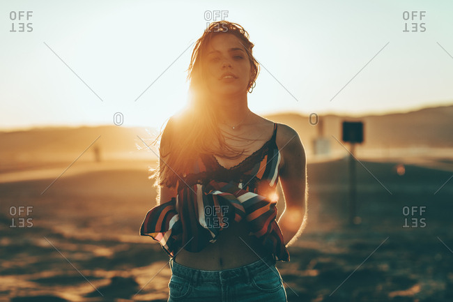 Portrait of a young woman standing outside at sunset
