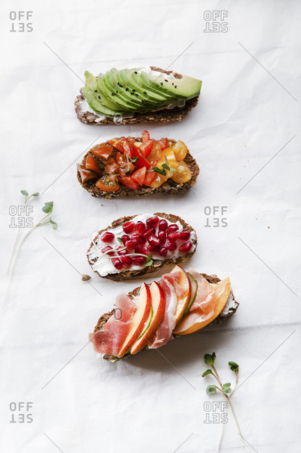 Variety of bruschettas with avocado, prosciutto, tomatoes and pomegranate seeds on white background