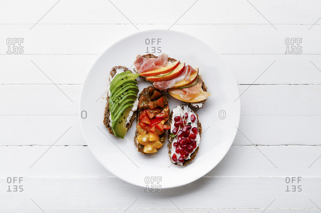 Variety of bruschettas with avocado, prosciutto, tomatoes and pomegranate seeds on white plate