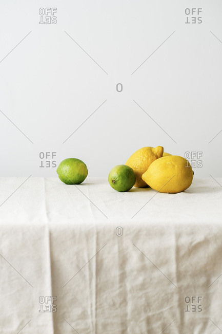 Minimalistic composition with citrus fruits on a table covered with white linen tablecloth