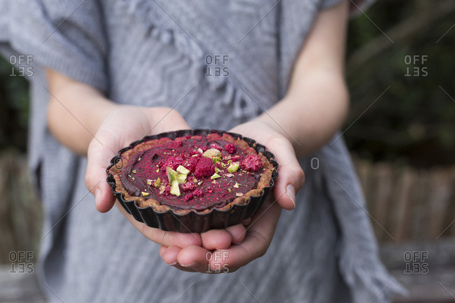 Spiced chocolate tarts being held in a girls hands
