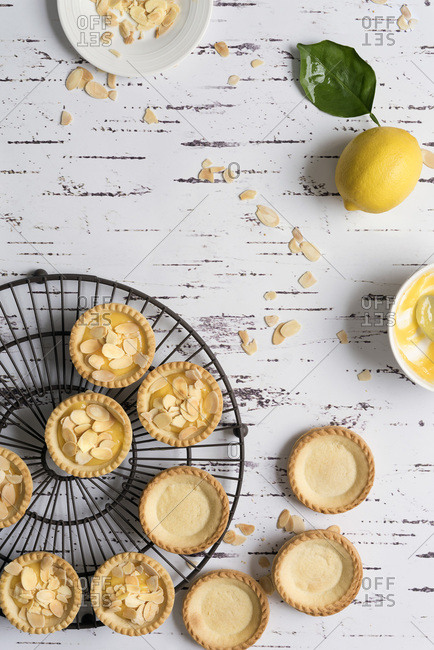 Small round pastry cases unfilled and filled with lemon butter and decorated with toasted almond flakes