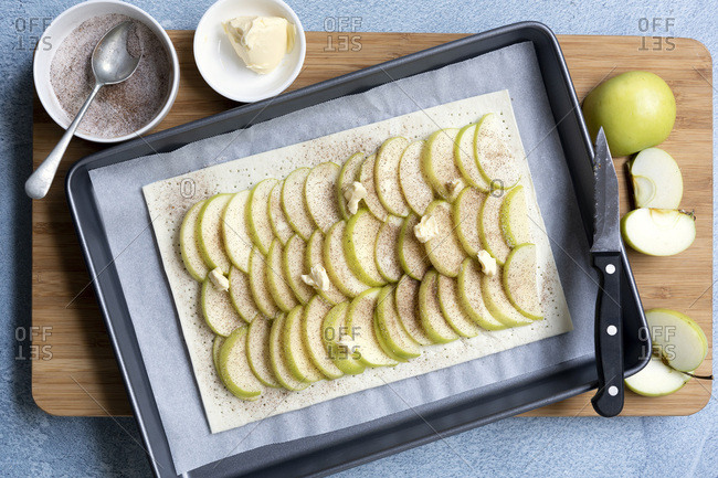 An uncooked apple tart with rows of sliced green apples on pastry, a sprinkling of cinnamon sugar and dots of butter