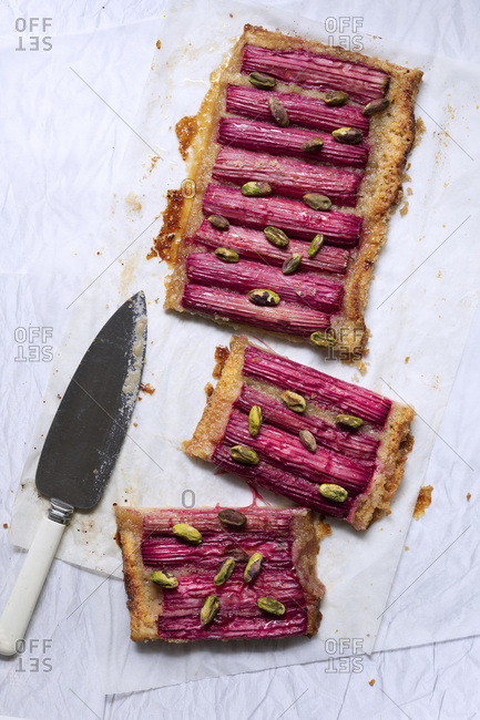 A rhubarb and pistachio nut tart on baking paper with a knife