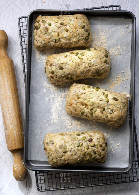 Pumpkin seed bread rolls on a baking tray with a rolling pin