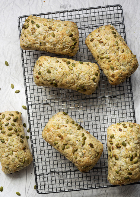Pumpkin seed bread rolls cooling on a wire cake rack