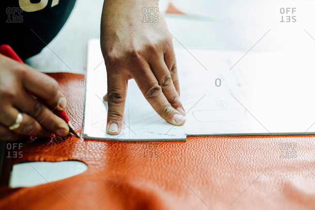 Person making a sewing pattern for a bag on processed leather
