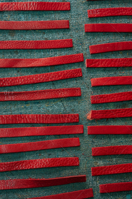 Red leather straps pattern on grey background