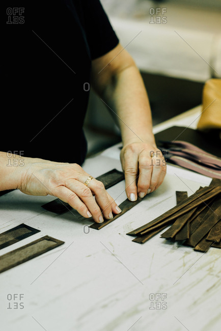 Hands putting together leather parts