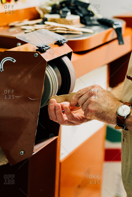 Person working on a leather bag parts with a machine