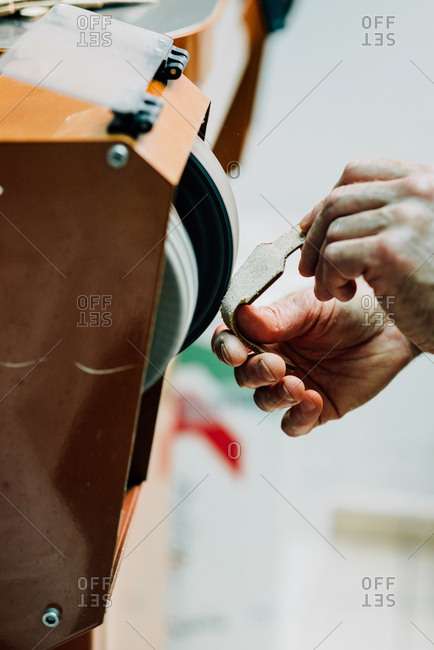 Person working on a leather bag pieces with a machine