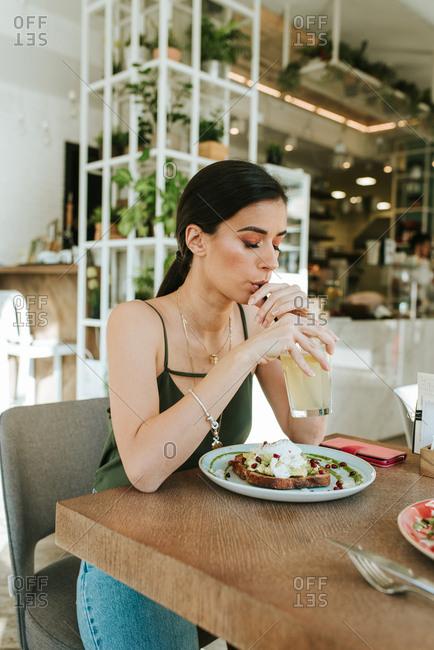 Woman drinking lemonade and eating avocado toast