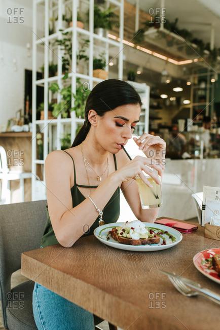 Woman drinking lemonade and eating avocado toast at a restaurant