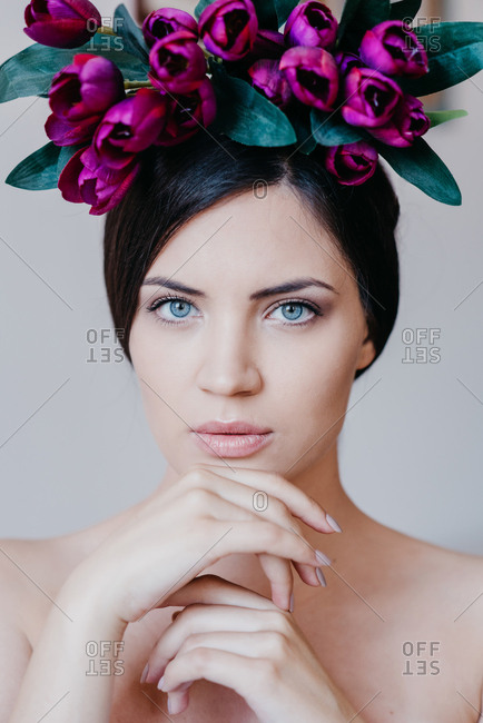 Portrait of beautiful brunette woman with blue eyes with purple tulips on her head