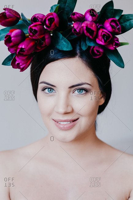 Beautiful brunette woman with blue eyes with purple tulips on her head