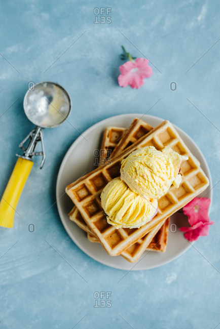 Overhead shot of waffles with scoops of vanilla ice cream on blue background