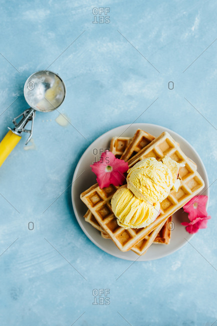 Top view of waffles with vanilla ice cream on blue background