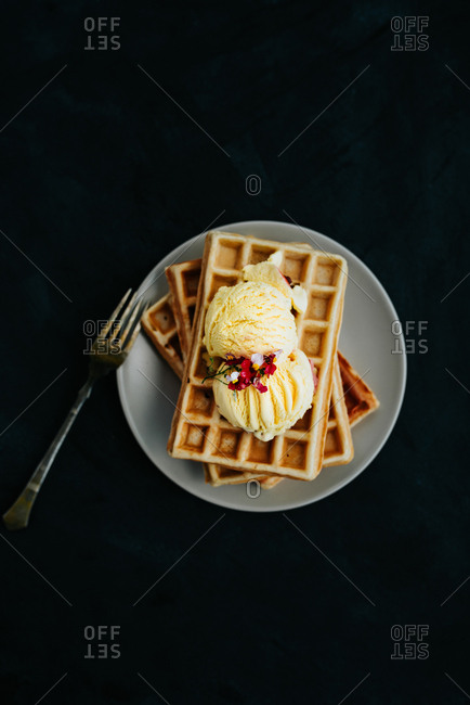 High angle view of waffles with vanilla ice cream on dark background