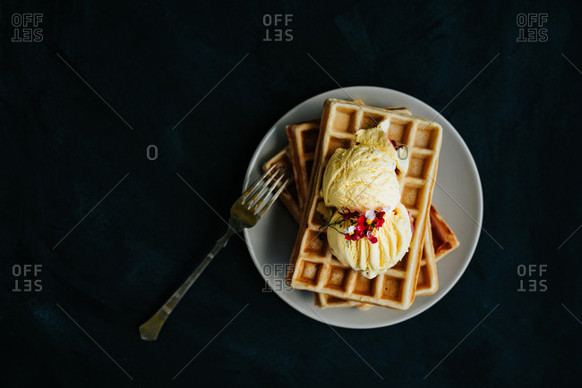 Top view of waffles with vanilla ice cream on dark background