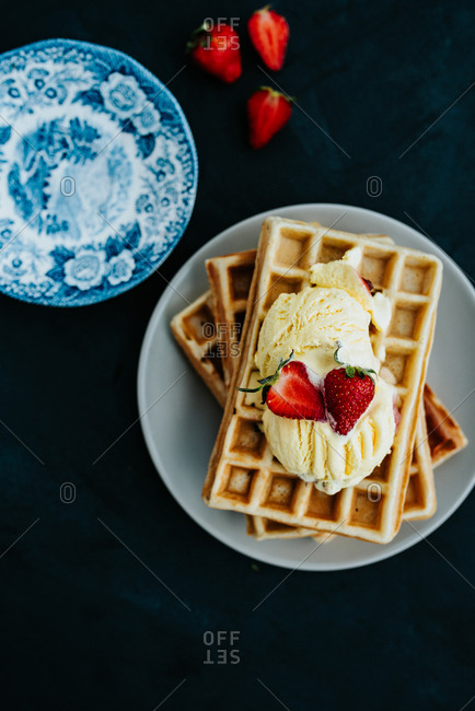 Top view of waffles with vanilla ice cream on a plate next to strawberries