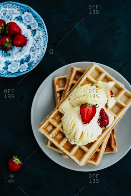 Close up of waffles with vanilla ice cream on a plate next to strawberries