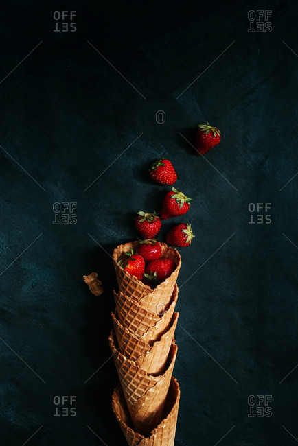 Stack of ice cream cones filled with fresh strawberries on a black background