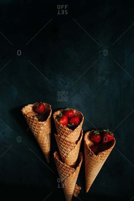 Stacks of ice cream cones filled with fresh strawberries on a black background