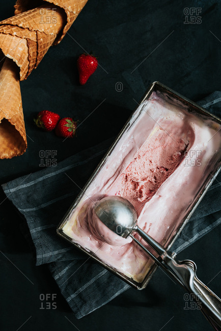 Strawberry ice cream in a dish on a black background with cones