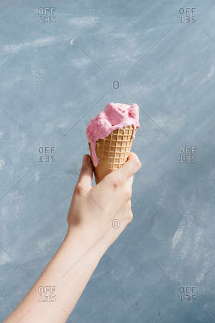 Hand holding an ice cream cone as it melts