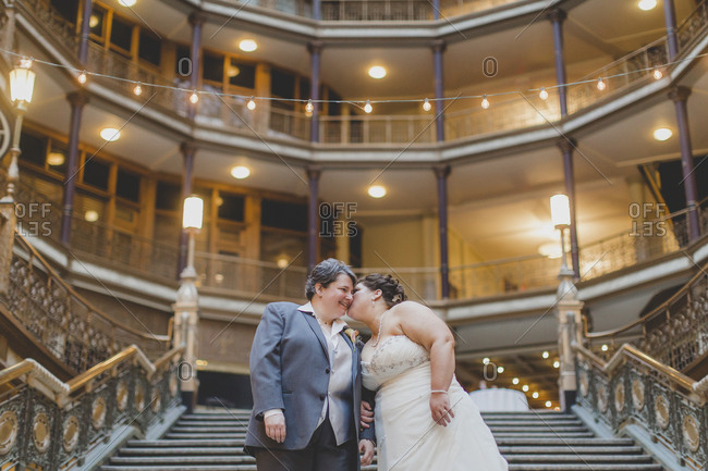 A lesbian couple share a tender kiss and smile on a grand staircase before entering their wedding reception