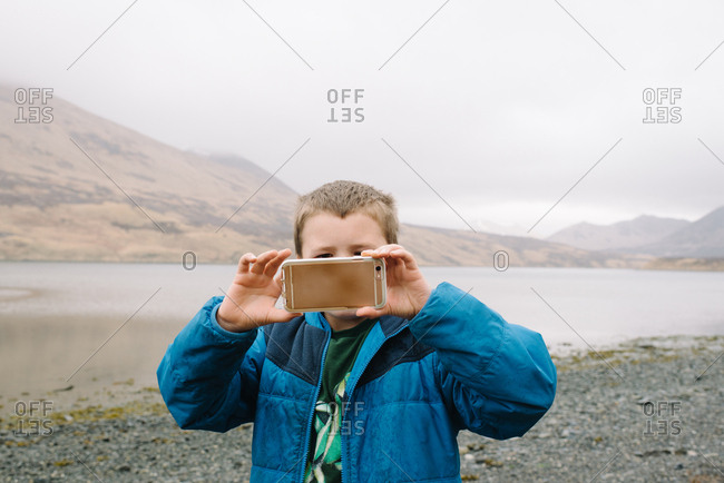 Boy taking pictures with cell phone in rural Alaska