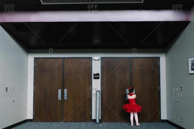 Little girl behind doors backstage wearing ballet costume