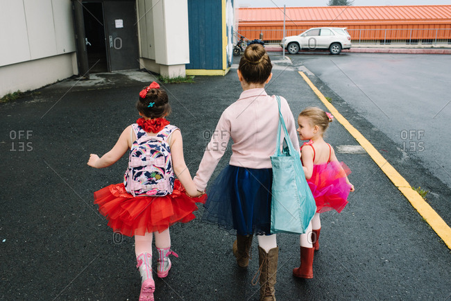 Three girls walking hand in hand in ballet outfits
